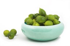 Bowl of key limes. Key limes in turquoise bowl royalty free stock photography