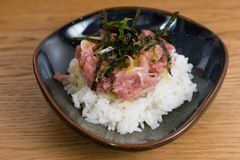 Bowl with Kobe Beef tartare served with fried nori seaweed, egg yolk, chopped onion, over a bed of steamed white rice. Bowl with Kobe Beef tartare with egg yolk royalty free stock photos