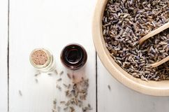 Bowl of Lavender Buds with Glass Oil Vials on White Wood Planked Table From Above stock photo