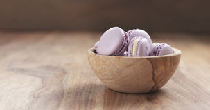 Bowl with lavender violet macarons on table Stock Photo