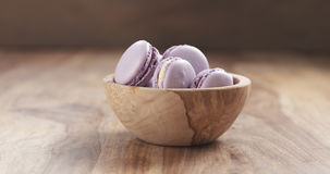 Bowl with lavender violet macarons on table Stock Photography