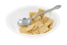 A bowl with leftover whole wheat cereal and spoon. A bowl of leftover whole wheat cereal with a spoon on a white background Stock Photos