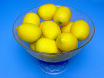 Bowl of lemons. A decorative bowl, engraved with floral patterns, full of lemons, viewed from about 45 degrees above and placed over a mid-blue background Stock Photography