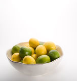 Bowl of lemons and limes on white. Stock Photography