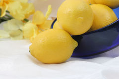 Bowl of lemons on silk Royalty Free Stock Photos