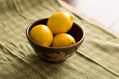 Bowl of Lemons. Three lemons in a brown bowl sitting on a green cloth Royalty Free Stock Image