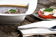 Bowl of Lentil soup. With sliced tomato on the side Stock Photography