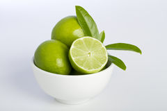 Bowl of Limes. And leaves Stock Images