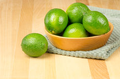 Bowl of limes on green cloth Royalty Free Stock Image