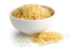 Bowl of long grain parboiled rice isolated on white. Spilled ric Royalty Free Stock Photos