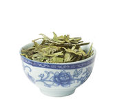 Bowl with loose green dry tea,  isolated. Bowl with loose green dry tea, long leaves variety,  isolated on white Royalty Free Stock Images