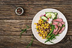 Bowl lunch with grilled beef steak and quinoa, corn, cucumber, radish and arugula stock photos