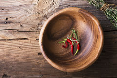 Bowl made of wood with  simple wooden rustic background  red peppers and sharp beam thyme tied  cotton twine. View from Stock Photo