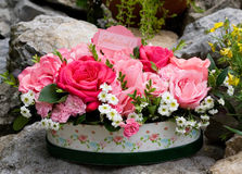 Bowl of mainly pink and red roses. Decorated bowl of pink and red roses and white daisy-like flowers with a garden rockery behind Royalty Free Stock Photo