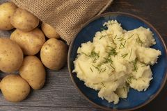 Mash potato topped with chives and a sack of whole potatoes stock photos