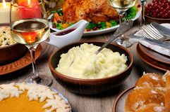 Thanksgiving Day. A bowl of mashed potatoes on a table among the pumpkin pie, baked turkey, cranberry-orange sauce,   a glass of white wine for Thanksgiving Royalty Free Stock Photography