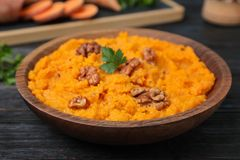 Bowl with mashed sweet potatoes on wooden. Table royalty free stock photography