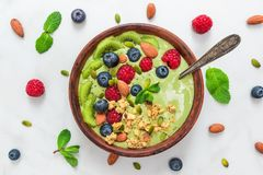 Bowl of matcha green tea smoothie with fresh berries, nuts, seeds and oat granola with a spoon for healthy breakfast stock image