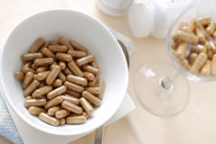 Bowl of medical capsules and beverage Royalty Free Stock Photography