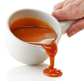 Bowl of melted caramel sauce. On a white background royalty free stock photo