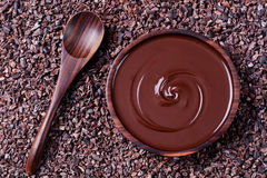 Bowl of melted chocolate and wooden spoon on a crushed raw cocoa beans, nibs background. Copy space Top view Stock Photo