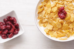 Bowl of milk with corn flakes and cranberries Stock Photos
