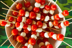 Bowl of mini mozzarella balls and cherry tomato skewers. Bowl on green camouflage tablecloth holding multiple skewers of mini mozzarella cheese balls and cherry Royalty Free Stock Image