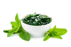 Bowl of mint jelly. White bowl of mint jelly with mint leaves on white Stock Image
