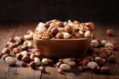 Bowl of mix of nuts. On wooden table stock images