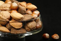 Bowl of mixed nuts. Glass bowl filled with mixed nuts on a black background Stock Photography