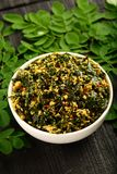 Bowl of moringa leaf stir fry vegan diet food. Healthy delicious vegetarian dish made of moringa leaf and spices on a rustic background stock images