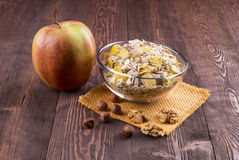 Bowl of muesli, apple, nuts, flakes, candied  for a nutritious b Royalty Free Stock Photo