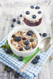 Bowl of muesli with fresh blueberries and glass of yogurt on whi Stock Photo