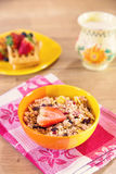 Bowl of muesli with fruit and milk in the background. For a healthy breakfast Royalty Free Stock Photos