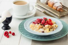 Bowl of muesli with yoghurt strawberries and blueberries boiled egg orange juice croissant and coffee for healthy breakfast royalty free stock photography