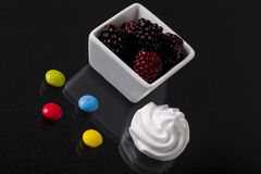 A bowl of mulberry with whipped cream and colorful chocolate dra Stock Photos