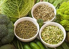 Bowl of mung beans and split peas and pumkin seeds with raw organic green toned vegetables. Macro royalty free stock photography
