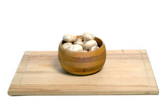 Bowl Of Mushrooms. A wooden bowl of aged mushrooms shot on a wood cutting board, isolated against a white background Stock Images
