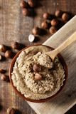 Bowl with natural hazelnut paste. High angle view of a brown earthenware bowl with natural hazelnut paste and some shelled hazelnuts on a rustic wooden table Stock Photo