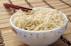 Bowl of noodels and chopsticks. A bowl of noodles focus in on the tip of chopsticks Stock Images