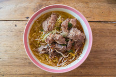 Bowl of noodles with pork on wooden table. Bowl of spicy noodles with pork  cartilage on wooden table stock photos