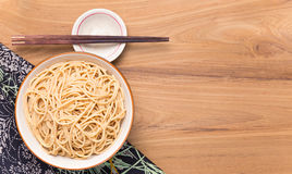 Bowl of noodles with wooden chopsticks on wooden table Stock Photo