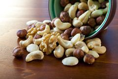 Bowl with nuts. Nuts spilling out of a small bowl Royalty Free Stock Photography