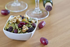 Bowl of nuts seeds with blurred wine bottle and glass in the background. Healthy seeds and nuts in a white bowl on the table with wine bootle and glass Royalty Free Stock Photography