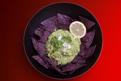 Bowl O' Guacamole. A bowl of guacamole on a red background Stock Image