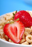 Bowl of oat cereal with strawberries. Bowl of crispy oat cereal with fresh blueberries stock photos