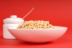 Bowl of oat cereal with sugar bowl on red background Royalty Free Stock Image