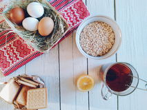 Bowl with oat flakes, lemon, a cup of tea, biscuits and eggs lie on white boards.  Royalty Free Stock Photos
