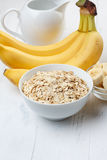 Bowl of oat flakes with sliced banana. Close-up on wooden table Royalty Free Stock Image