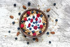 Bowl of oat granola with greek yogurt, fresh raspberries, blueberries and nuts. On white wooden table for healthy breakfast, top view Stock Images